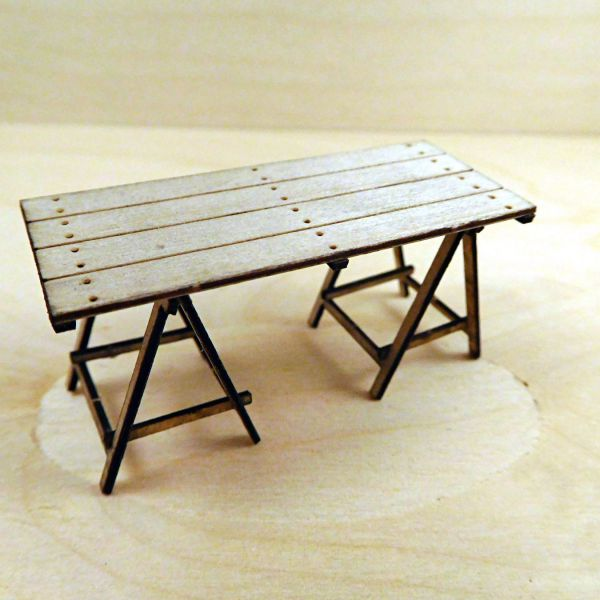 <p>This set contains parts to assemble one table, resting on 2 pairs of trestles. The table's surface is engraved with panel/planking-lines and nailheads; the underside features 3 lateral support-boards.<br />