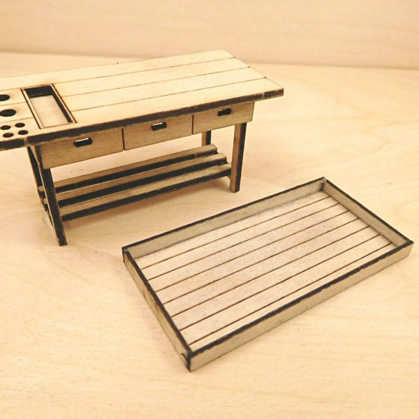<p>This set features parts to build a detailed workbench and toolrack. The bench's top surface features engraved panel lines, a sunken tool-tray and several holes/slots to hang tools in. Its frame features 3 horizontal boards and the front side is engraved to resemble 3 drawer-fronts. The toolboard features engraved panel lines.<br />