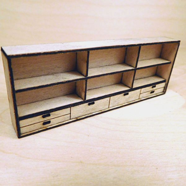 <p>This set contains parts to assemble a wall-mounted shelving unit with 6 compartments. The shelves and upright supports slot in place, to be attached to the backboard. The front features engraved detail resembling 6 drawer-fronts. <br />