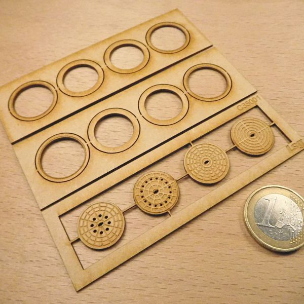 <p>This set contains parts to assemble 4 manhole covers, featuring both the outer rings and the actual covers – which are engraved in 4 different styles.<br />